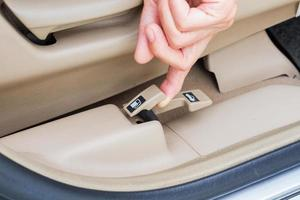 closeup mão puxando o botão de abertura da porta de combustível em um carro foto