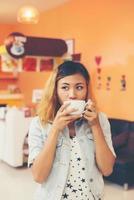 jovem mulher bonita bebendo café cappuccino quente no café. foto