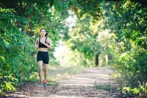 mulher jovem aptidão correndo em uma estrada rural. mulher esporte correndo. foto