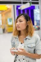jovem mensagens de texto no smartphone andando no shopping. foto