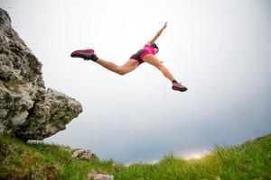 salto de uma atleta mulher esportiva correndo nas montanhas foto