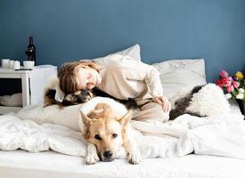 jovem feliz sentada na cama brincando com seus cachorros foto