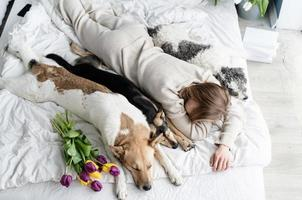 jovem de pijama deitada na cama com seus cachorros foto