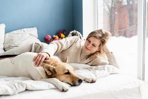 jovem feliz deitada na cama com seus cachorros foto