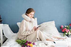 mulher sentada na cama de pijama digitando uma mensagem no telefone foto