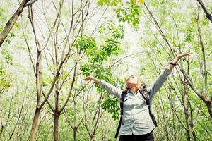 mochila de mulher andando na floresta esticar as mãos felizes com ar fresco foto