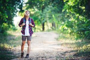 jovem alpinista com mochila caminhando e sorrindo em uma trilha no campo foto