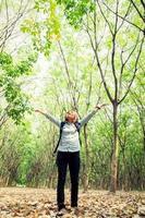 jovem caminhando na floresta, levantando as mãos felizes com ar fresco. foto