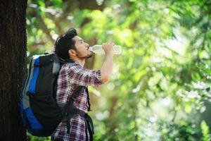 jovem com sede e bebe água durante a caminhada atrás de uma grande árvore. foto