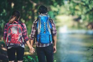 casal caminhando na floresta juntos. férias de viagens de aventura. foto