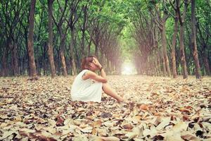 mulher triste tira as mãos do rosto tão tristemente sentada na folha seca. foto