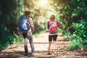parte traseira do casal caminhando. viagem de aventura do casal. foto