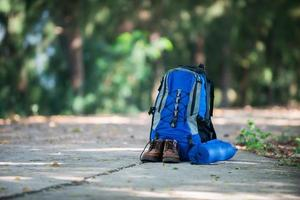 mochila e sapatos mochileiros descansam na estrada enquanto fazem caminhadas. foto
