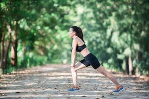 mulher jovem aptidão esticando as pernas antes de correr. foto