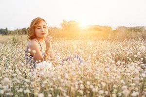 Mulher bonita e sexy sentada em um campo de flores, desfrutar e cheirar uma flor foto