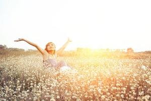 mulher sentada em um campo de flores levantando ar fresco pela manhã foto