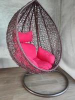 balanço pendurado com suporte e travesseiro macio vermelho no canto da sala foto