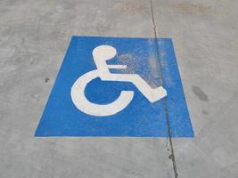 sinal azul no asfalto sobre estacionamento para deficientes físicos foto