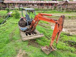 velha escavadeira amarela quebrada no campo de arroz, Tailândia. foto