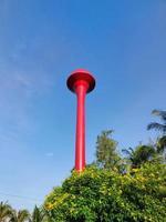 tanque de torre de água vermelha tailandesa com céu azul. foto vertical.