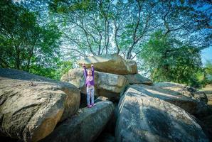 menina em pé com as mãos levantadas no fundo da rocha e da árvore foto