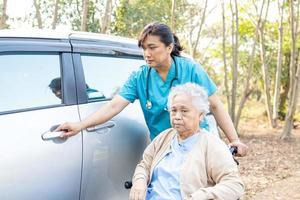 Paciente asiática sênior, mulher sentada em uma cadeira de rodas, chegar ao carro foto