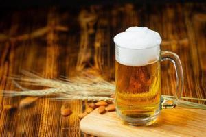 um copo de cerveja é colocado no chão de madeira. foto