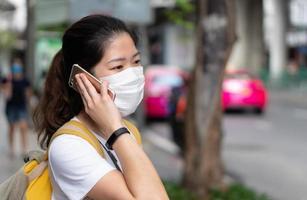 jovem usando máscara usando smartphone durante o covid 19 surto. foto
