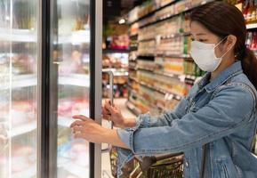 jovem mulher asiática usando máscara enquanto faz compras no supermercado foto