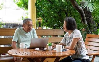 casal sênior asiático sentado e se divertindo juntos foto