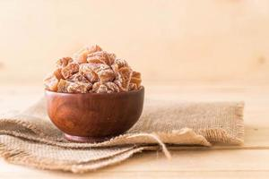 ameixas secas em tigela de madeira foto