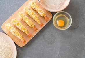 Camarões fritos em massa na tábua de madeira com ingredientes foto