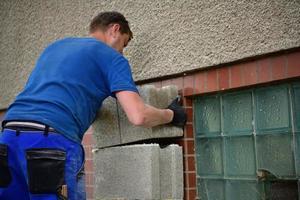 o pedreiro coloca blocos pré-fabricados de concreto na parede foto