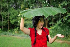mulher asiática estava sob uma folha de bananeira se abrigando da chuva foto
