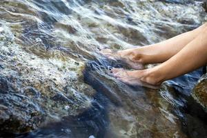pé de mulher jovem na água do mar limpa foto