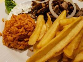 giroscópios de comida grega com batatas fritas e salada foto