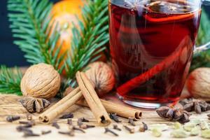 vinho quente e especiarias de natal em madeira de oliveira foto