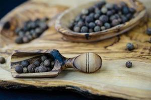 algumas bolas de pimenta da Jamaica em madeira de oliveira foto