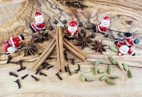 bonecos de papai noel e especiarias de natal em madeira de oliveira foto