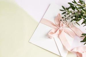 envelope em um fundo branco-rosa com fita de seda pêssego, flores. foto