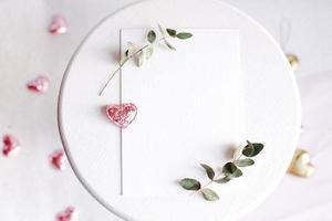 fundo com espaço de cópia em branco na mesa, coração de purpurina, eucalipto foto
