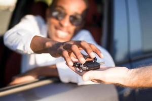 feliz afro-americano em um carro com uma chave, no verão foto