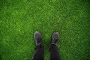 feche a foto do pé do homem na grama verde do estádio