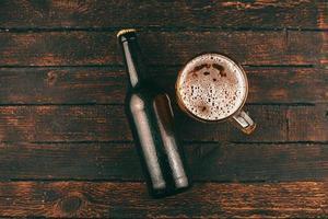 foto de vista superior de garrafa de cerveja e copo de cerveja sobre fundo de madeira