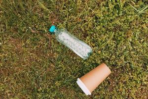 garrafa de plástico e xícara de café de papel na grama verde, conceito de lixo foto