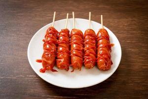 espeto de linguiça frita com ketchup no prato branco foto