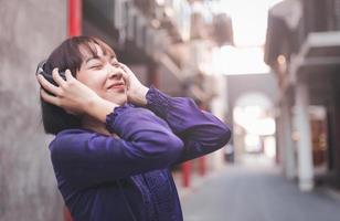 jovem asiática feliz ouvindo música com fones de ouvido foto