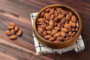 amêndoas em tigela de madeira sobre a mesa, lanche saudável, comida vegetariana foto