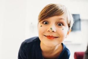 um menino fofo com o rosto pintado de palhaço com cor creme comestível foto