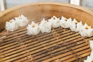 pão chinês quente com dim sum de bambu foto
